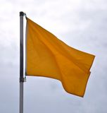 Beach Caution Flag. With grey sky Stock Photo