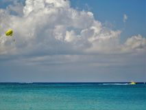 On a beach in Cayman Island. An air balloon flying over a Cayman Island beach and a speed boat passing by Stock Photo