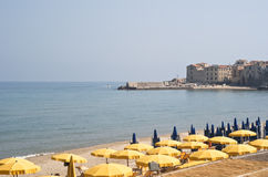 Beach of Cefalù. With yellow umbrellas royalty free stock photography