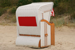 Beach chair. White wicker beach chair typical for the Baltic Sea, Germany. Red sign on rear is suitable for adding text Royalty Free Stock Photo