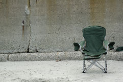 Beach chair. A green cloth lounge chair in the sand, against a concrete retaining wall Royalty Free Stock Photography