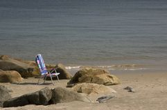 Beach Chair. A beach chair sitting amongst the rocks on the shoreline Royalty Free Stock Photography