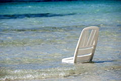 Beach chair. A white beach chair stand in the water at the beach stock images