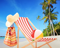 Beach chair with accessories on a tropical beach with palms. Beach chair with accessories on a tropical beach with palm trees Royalty Free Stock Photo