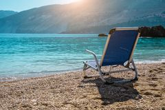 Beach chair from back on tranquil pebble beach. Amazing view to impressive rocks in the water. Serenity and isolation on. Holiday stock photo