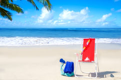 Beach chair and bag with flip flops by the ocean Stock Photography