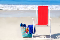 Beach chair and bag with flip flops by the ocean Royalty Free Stock Photography