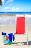 Beach chair and bag with flip flops by the ocean Stock Images