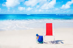 Beach chair and bag with flip flops by the ocean Royalty Free Stock Image