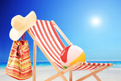 Beach chair with ball, bag and hat by the sea Stock Photo