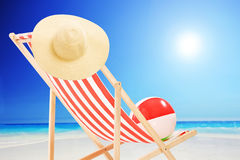Beach chair with ball and hat by the sea Royalty Free Stock Photography