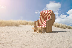 Beach chair on baltic sea beach. Traditional canopied beach chair at baltic sea beach with marram grass covered dunes and blue sky in background Royalty Free Stock Images