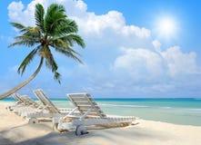 Beach chair on beach with blue sky. Tropical beach with a sun-lounger facing the blue sea Stock Image
