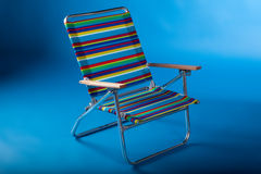 Beach chair in blue II. Colorful beach chair isolated in blue background Royalty Free Stock Photo