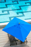 Beach chair and blue umbrella by the pool Stock Photography