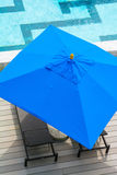 Beach chair and blue umbrella by the pool Royalty Free Stock Images
