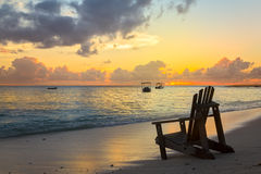 Beach chair on the coast line by sunset Stock Images