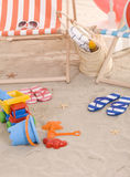 Beach chair with colorful sand toys Royalty Free Stock Images
