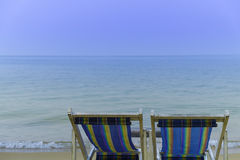 Beach chair facing beautiful calm sea. Two colorful beach chair facing beautiful calm sea with clear blue sky Royalty Free Stock Photos