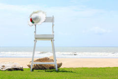 Beach chair on green grass, white sand and sea on blue sky background. White beach chair on green grass, white sand and sea on blue sky background royalty free stock images
