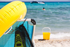 Beach chair with inflatable float and toys on beach. Royalty Free Stock Image