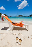Beach chair with orange towel and coconut drink Stock Images