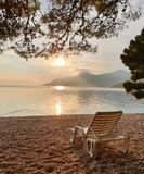 Beach chair on a pebble beach against the background of a calm clean sea, mountains and sunset.  Summer vacation at sea. Folded, chairs, backdrop, relax stock image