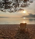 Beach chair on a pebble beach against the background of a calm clean sea, mountains and sunset.  Summer vacation at sea.  Relax. Pine, boat stock images