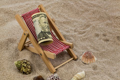 Beach chair with piggy bank and dollars Royalty Free Stock Photography