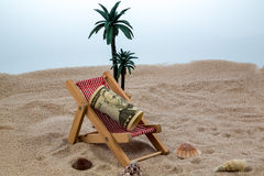 Beach chair with piggy bank and dollars Royalty Free Stock Image