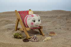 Beach chair with piggy bank and euro Stock Image