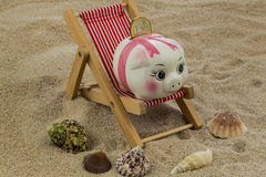 Beach chair with piggy bank and euro Stock Photos