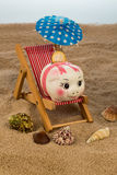 Beach chair with piggy bank and euro Royalty Free Stock Photography