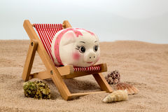 Beach chair with piggy bank Royalty Free Stock Photos