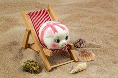 Beach chair with piggy bank Stock Photos