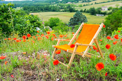 Beach chair in red poppies in France Stock Photo