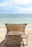 Beach Chair and Sail Boat. Image of a chair on the beach with a sailboat on the horizon Stock Photos