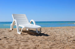 Beach chair on the sand. With sea on background Stock Photos