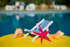 Beach chair and shells at swimming pool Stock Images