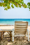 Beach chair and side table are on sand beach Stock Images