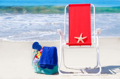 Beach chair with starfish and bag by the ocean Stock Image