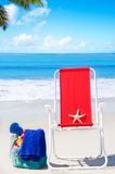 Beach chair with starfish and bag by the ocean Stock Photos