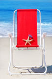 Beach chair with starfish and bag by the ocean Royalty Free Stock Image