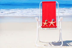 Beach chair with starfishes and bag by the ocean Royalty Free Stock Photos