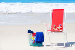 Beach chair with starfishes and bag by the ocean Royalty Free Stock Images