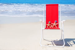 Beach chair with starfishes by the ocean Stock Photos