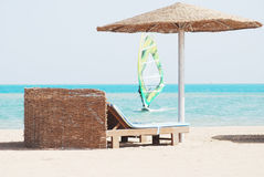 Beach chair with straw sunshade. At the sea and windsurfer Royalty Free Stock Photography