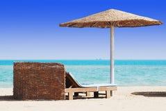 Beach chair with straw sunshade. Empty beach chair with straw sunshade at the sea Stock Photo