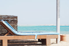 Beach chair with straw sunshade. Empty beach chair with straw sunshade at the sea Stock Images