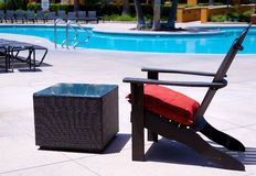 Beach chair and table by a pool Royalty Free Stock Photography